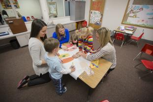 Young children sitting around table with teacher engaging in learning activities that support the Pyramid Model for Early Education