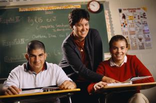 Teacher and two adolescent students at desks
